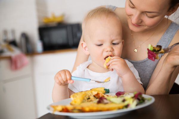 Child eating omelette and salad