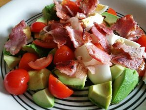 Egg, tomato, avocado and warm bacon salad